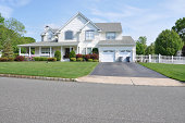Two story double car garage with trash can containers landscaped front yard beautiful large suburban home