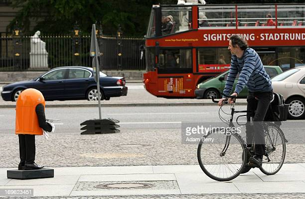 A trash canshaped robotic butler named Reiner belonging to the Berliner Stadtreinigungsbetriebe city garbage removal company speaks to a cyclist...