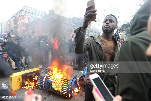 A trash fire set by antiTrump protesters burns on K Street on January 20 2017 in Washington DC Whille protests were mostly peaceful some turned...