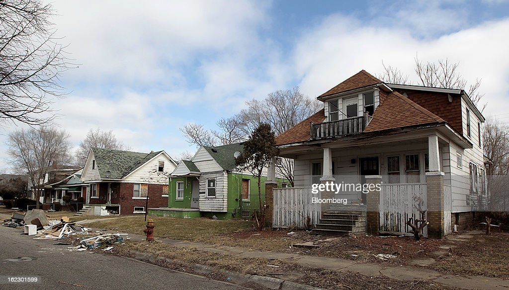 Trash sits in front of dilapidated houses on Mackay Street in Detroit, Michigan, U.S., on Thursday, Feb. 21, 2013. A fiscal emergency grips Detroit, according to a report ordered by Governor Rick Snyder, that opens a path to a state takeover of General Motors Co.'s home town, citing deficits that have stymied city officials after a $326.6 million gap last year. Photographer: Jeff Kowalsky/Bloomberg via Getty Images