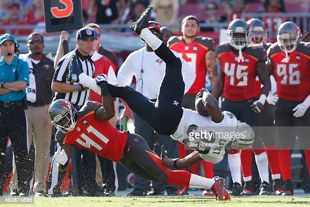 Travaris Cadet of the New Orleans Saints gets tripped up along the sideline by CJ Wilson of the Tampa Bay Buccaneers in the second half of the game...