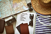 Top view of traveler's accessories and travel checklist. Vintage style photo filter with grain and vignette added.