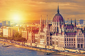 Travel and european tourism concept. Parliament and riverside in Budapest Hungary with sightseeing ships during summer day sunset