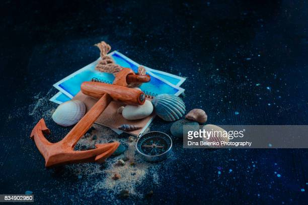 Travel background with wooden anchor, compass, magnifying glass, watercolor sketches, stones, seashells and sand. Copy space.