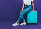 A young woman in blue jeans is sitting on a blue suitcase on a purple background