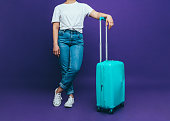 A young woman in a white T-shirt and blue jeans is standing near to a light blue suitcase on a lilac background Close-up photo
