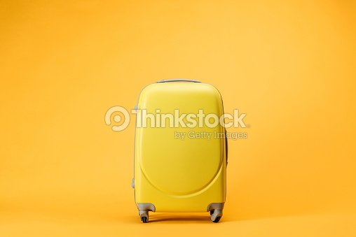 travel bag with wheels on yellow background : Stock Photo