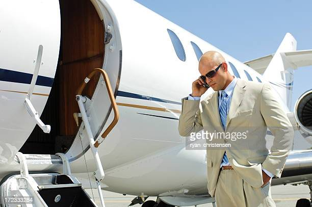 Travel - Businessman talking on phone by private jet.