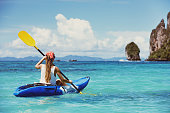 Girl on single kayak or canoe swims at tropical sea bay. Travel or kayaking concept