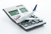 Miniature airplane model with calculator for travel budget, cost or expenses concept