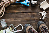 Top view of travel equipment for a mountain trip on a rustic dark wood floor with empty space in the middle. Items include flask, map, knife, rope, carabiner, flashlight, shoes, GPS