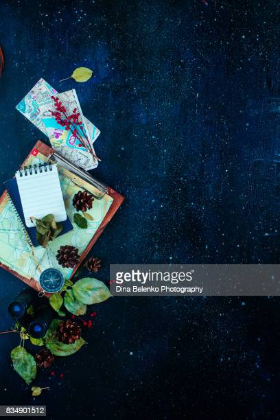 Travel essentials dark copy space background with adventure glass jar, leaves, notes, map, pine cones, binoculars and coins.