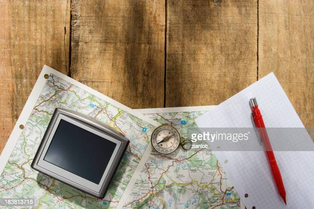 Travel Gear. GPS, compass and map on rustic wood.