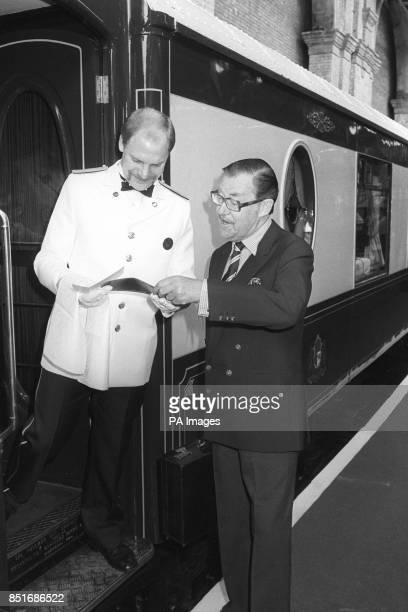 Travel journalist Alan Whicker checks his ticket with a porter before boarding the VeniceSimplon Orient Express which is leaving from Victoria...