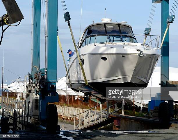 A travel lift hoists a boat out of the water as workers at Port Harbor Marina in South Portland haul and winterize over 300 boats