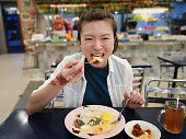 A lady enjoying local banana leaf nasi lemak (coconut milk rice with fried egg, peanut and cooked chilli side).