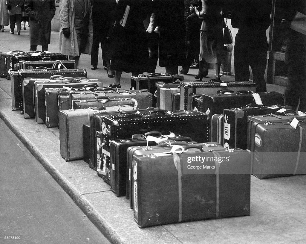 Travel luggage with tags lined up on sidewalk : Stock Photo