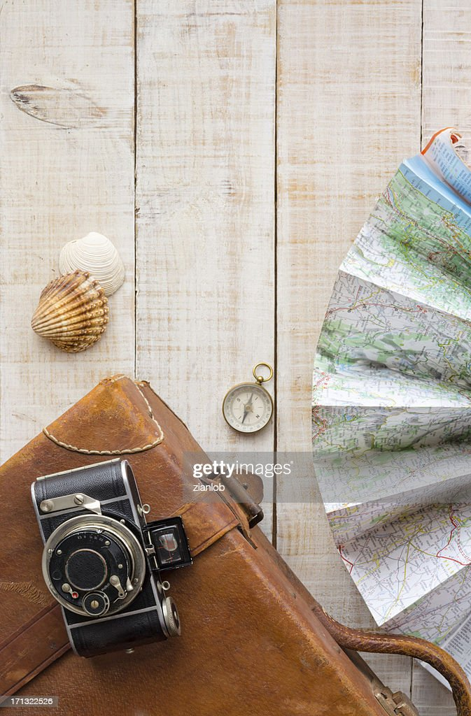 Travel objects. Suitcase, camera, map, compass and shells. : Stock Photo