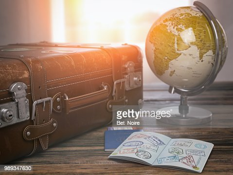 Concepto de viaje o turismo.  Antigua maleta abierta pasaporte con sellos de visa y globo. : Foto de stock