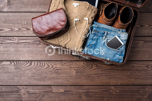 Travel preparations concept with open suitcase and woman's casual clothes : Stock Photo