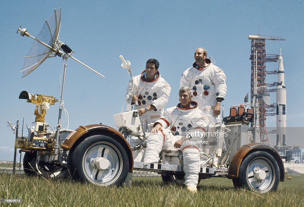 1972, USA, The American crew of NASA's 'Apollo 17' with the lunar rover and the Apollo rocket behind, Left-right, Harrison 'Jack' Schmitt (Lunar Module Pilot), Eugene Cernan, front (Commander) and Ron Evans (Command Module Pilot), 'Apollo 17' was the final lunar (moon) landing mission of the Apollo programme and the first launch at night
