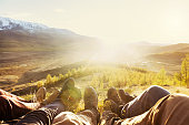 Five friends having rest on hilltop. Closeup photo of legs on mountains backdrop. Travel, tourism or trekking concept