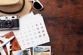 Travel vacation background concept with calendar, sun hat, camera, passport, airplane toy and weekend photos on wooden backdrop. Top view with copy space. Flat lay. All photos taken by me