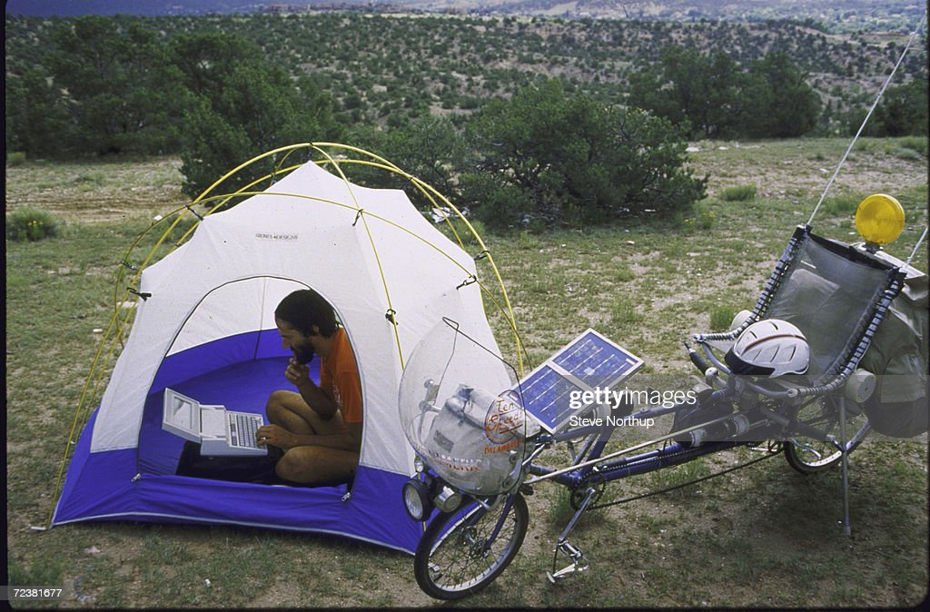 Travel writer Steve Roberts in tent, working with solar powered laptop computer, w, reclining bicycle outside; Rocky Mountains.