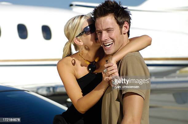Travel - Young couple having fun next to private jet