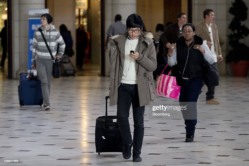 A traveler checks his phone while walking out of Union Station in Washington, D.C., U.S., on Wednesday, Nov. 21, 2012. U.S. travel during the Thanksgiving holiday weekend will rise a fourth straight year, gaining 0.7 percent from 2011, as trips by automobile rise even as airplane trips decline, AAA said last week. Photographer: Andrew Harrer/Bloomberg