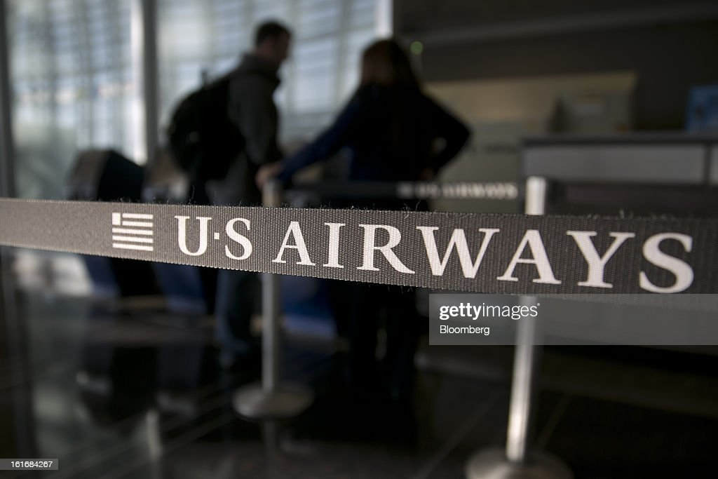 A traveler checks in at a US Airways Group Inc. counter at Reagan National Airport in Washington, D.C., U.S., on Thursday, Feb. 14, 2013. US Airways Group Inc., spurned in three prior merger attempts, will combine with bankrupt AMR Corp.'s American Airlines in an $11 billion deal to create the world's largest carrier. Photographer: Andrew Harrer/Bloomberg via Getty Images