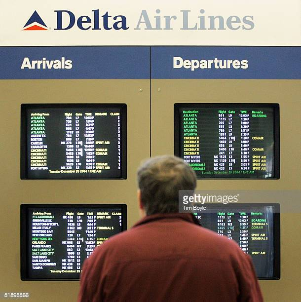 A traveler checks the Delta Air Lines/Comair Arrival/Departure board near the Delta Air Lines/Comair ticket counter area at O'Hare International...