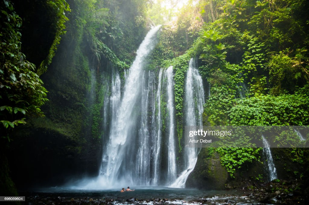 Traveler couple swimming in the beautiful wild waterfall in the deep rain forest of the national park of the Lombok island taken during travel vacations in Indonesia. : Stock Photo