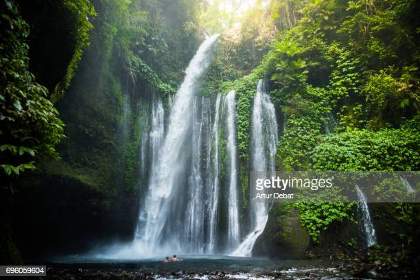 Traveler couple swimming in the beautiful wild waterfall in the deep rain forest of the national park of the Lombok island taken during travel vacations in Indonesia.