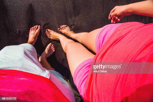 Traveler couple taking picture of legs on the black beach in the Tenerife island from personal perspective with vivid colors on clothes.