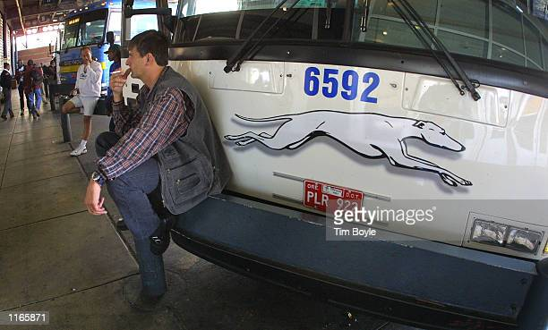 A traveler enroute to Madison Wisconsin smokes a cigarette October 3 2001 while he sits on the bumper of a Greyhound Bus at its Chicago terminal...