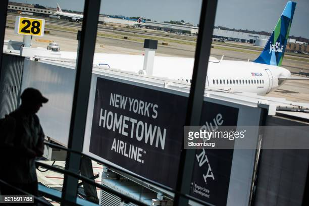 A traveler exits a gate at the JetBlue Airways Corp Terminal 5 inside John F Kennedy International Airport in New York US on Wednesday July 12 2017...