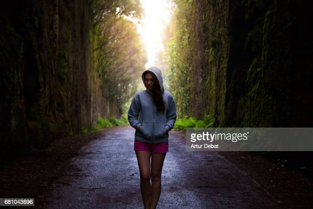 Traveler girl walking and enjoying a stunning walk in a road covered with rainforest deep vegetation and darkness during travel vacations in the north part of Tenerife island.