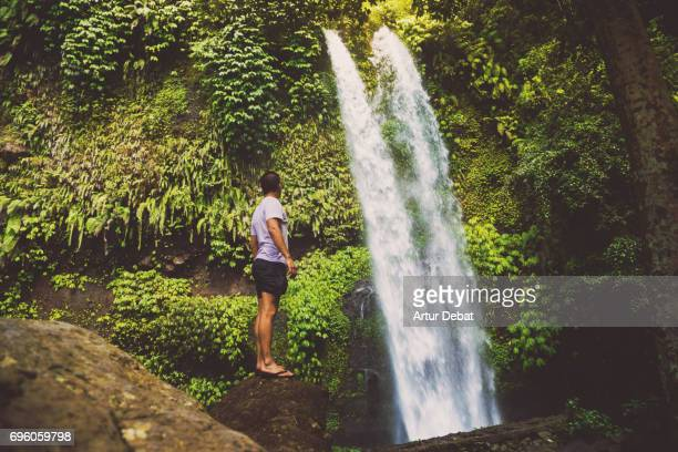 Traveler guy contemplating the beautiful wild waterfall in the deep rain forest of the national park of the Lombok island taken during travel vacations in Indonesia.