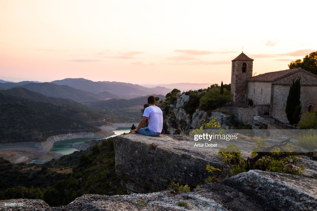 Traveler guy contemplating the view from the stunning Siurana town on top of cliff with amazing views during travel vacations in the Catalonia region. : Stock Photo