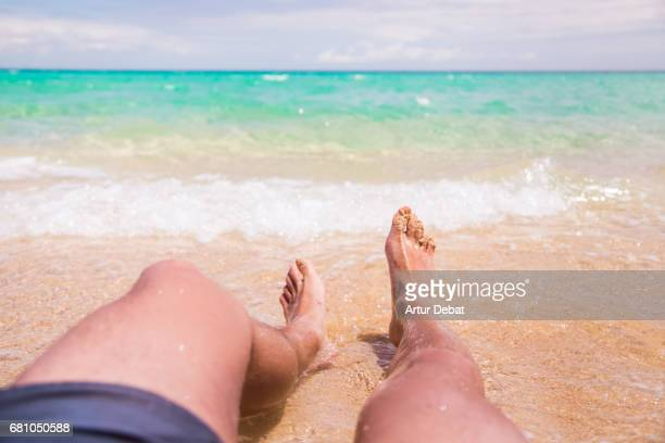 Traveler guy laying in the sand beach resting and contemplating the turquoise beautiful beach of Fuerteventura island during travel vacations.