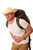 Traveler having stomach ache, nausea wearing straw hat, white shirt and backpack. Isolated over white.