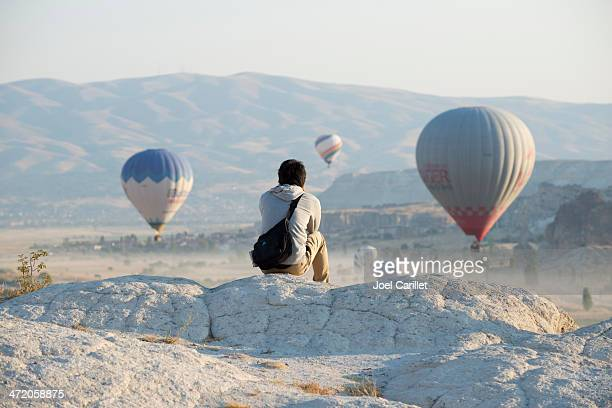 Traveler in Cappadocia, Turkey watching hot air balloons