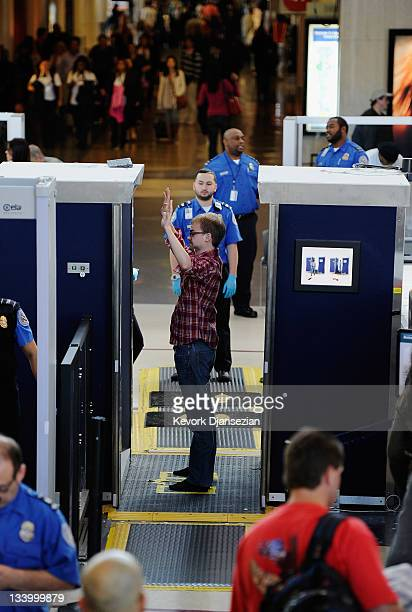 A traveler is screened by a body scanner at the security checkpoint of the American Airlines terminal at Los Angeles International Airport on...