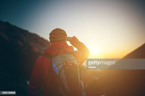 Traveler looking the sunrise on top of the mountain