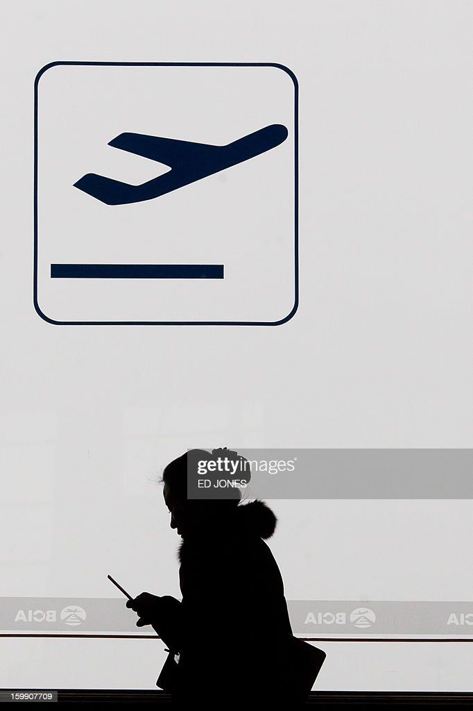 A traveler looks at her mobile phone at Beijing's international airport as some flights were delayed or cancelled due to poor visibility on January 23, 2013. China's capital Beijing will strengthen measures to combat pollution, state media reported, amid public anger over the dangerous air quality in the sprawling metropolis. AFP PHOTO / Ed Jones