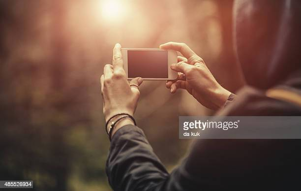 Traveler making selfie on smart phone in forest at sunset