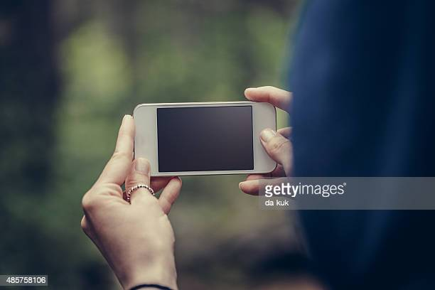 Traveler making selfie on smart phone in the forest