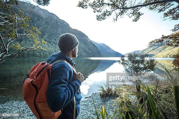 Traveler man by the mountain lake contemplates beautiful landscape