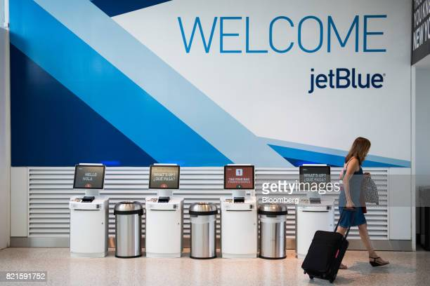 A traveler passes in front of self checkin kiosks at the JetBlue Airways Corp Terminal 5 inside John F Kennedy International Airport in New York US...